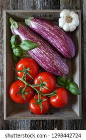 Raw vegetables: graffiti eggplants, garlic, tomatoes and basil  in tray, top view