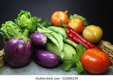 Raw vegetables on black background