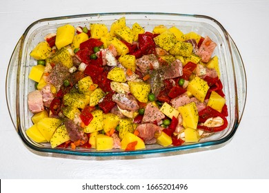 Raw vegetables ( potatoes, carrots, green peas, red pepper and onion) with pork meat garlic and spices in pyrex tray prepared for cooking in the oven.