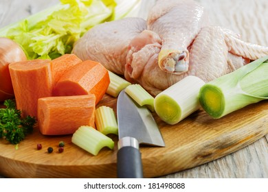raw vegetables and sliced ??chicken on a board