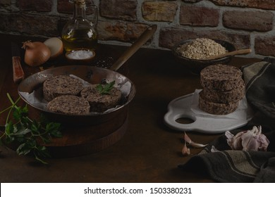 Raw veggie burger with black beans with parsley leaves on wood countertop.