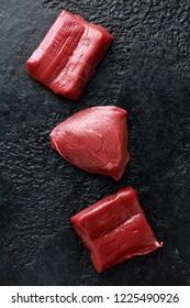 Raw venison steak on black rustic table..