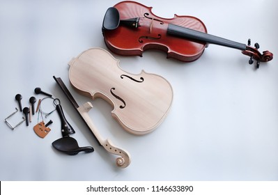 The raw violin and accessory put beside completed violin on white background
