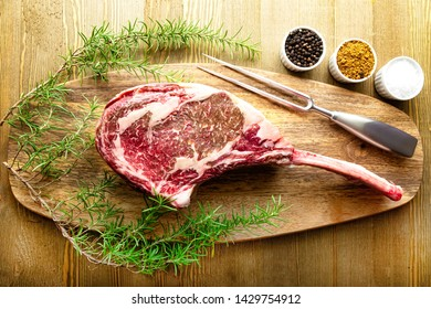 Raw waguy tomahawk steak on wooden background with spices ready forthe bbq