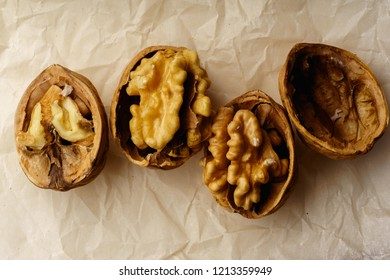 Raw walnuts in cracked nutshells on parchment paper. Overhead view
