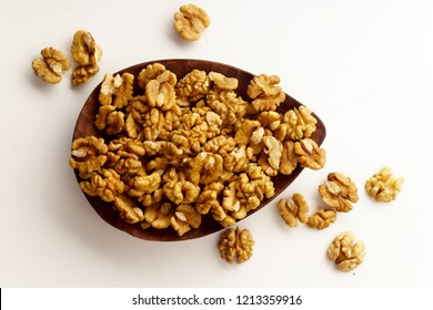 Raw walnuts on wooden tray on white background isolated with copy space. Overhead image