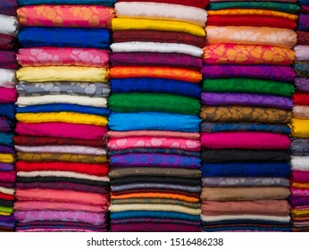 Raw and well arranged silk cloth yard goods in various colors at market stand in Hanoi, Vietnam