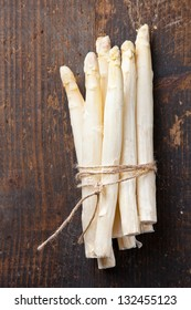 Raw white asparagus on wooden table