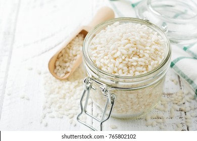 Raw  White rice variety Arborio for Italian risotto dishes in glass jar on  white concrete or stone background. Selective focus. Copy space.