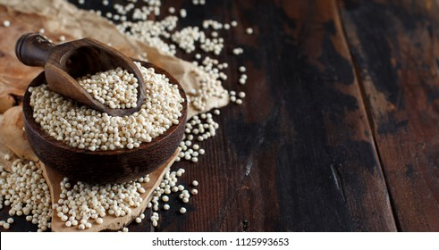 Raw White Sorghum grain in a bowl on a wooden table