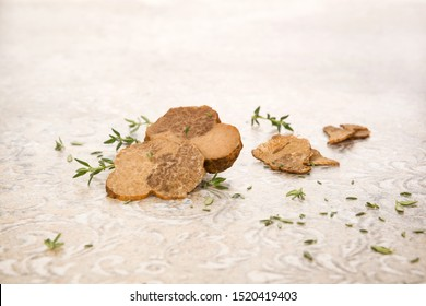 Raw white truffle mushrooms on the table with fresh herbs. Culinary gastronomy.