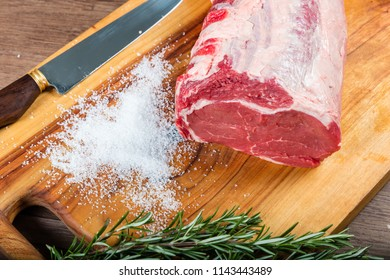Raw whole beef scotch fillet on chopping board with herbs