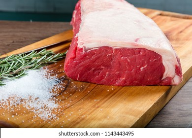 Raw whole beef sirloin on chopping board with herbs