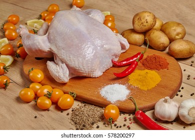 Raw whole chicken with ingredients for cooking: vegetables, spices and sliced lemon on a wooden board.  Horizontal. Close up view