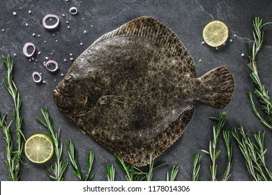 Raw whole flounder fish with rosemary on dark stone background. Creative layout made of fish, top view