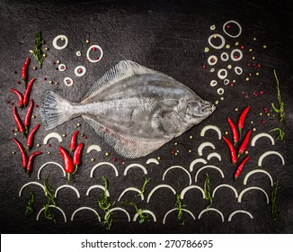 Raw whole flounder fish with spices,algae and onion on dark stone background , top view