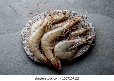 Raw whole fresh uncooked prawns shrimps on stone gray plate, stone background. Top view with copy space.