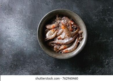 Raw whole fresh uncooked prawns shrimps on ice in vintage metal bowl over black texture background. Top view with copy space