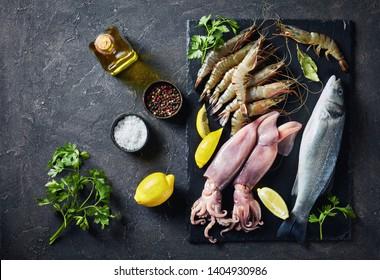 raw whole sea bass, king prawns, calamari, lemon slices, spices and herbs on a slate plate on a concrete table, view from above, close-up, flatlay