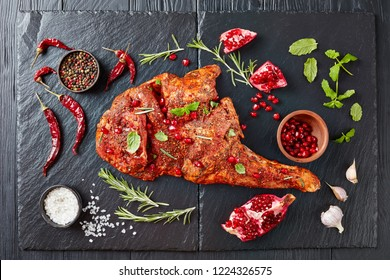 raw whole shoulder of a lamb marinated with all spices, mint and pomegranate seeds on a black stone tray, prepared to be roasted, view from above, flat lay, close-up