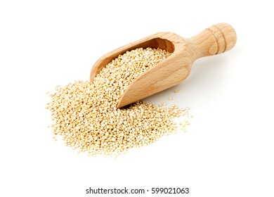 Raw, whole, unprocessed quinoa seed in wooden scoop over white background