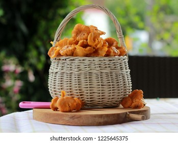 Raw wild chanterelles mushrooms in a basket in the garden. Organic Fresh chanterelle background on a table.