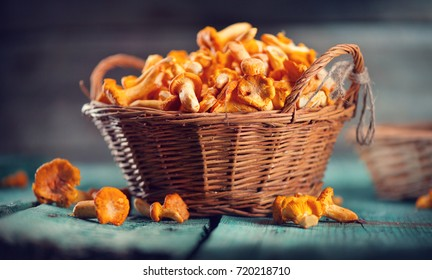 Raw wild chanterelles mushrooms in basket on old rustic wooden background. Organic Fresh chanterelle on a wood table. Soft focus