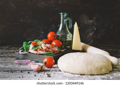 Raw yeast dough  and essential ingredients for pizza with bacon. Dark background