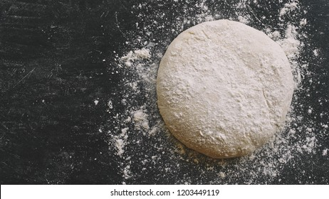 Raw yeast dough for pizza, bread or pasta. Dark food background. Copy space for text
