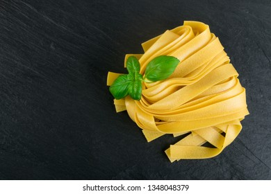 Raw yellow italian pasta pappardelle, fettuccine or tagliatelle close up. Egg homemade dry ribbon noodles, long rolled macaroni or uncooked spaghetti with basil