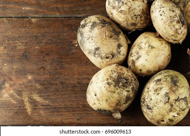 A lot of raw young potatoes on a wooden background, space for text