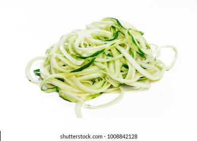 Raw zucchini noodles in a stack isolated on white