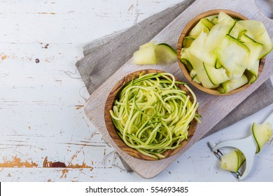 raw zucchini pasta on white background, copy space