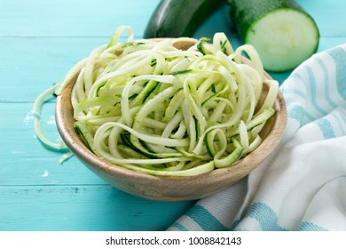 Raw zucchini spaghetti in a rustic wooden bowl on a turquoise wooden table