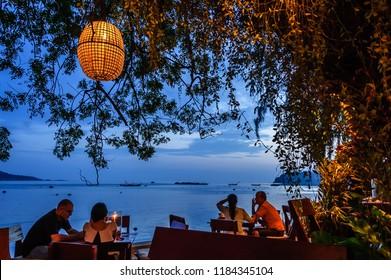 Rawai beach, Phuket, Thailand - January 2, 2014: Diners sit just after sunset at Nikitas Beach Restaurant on Rawai beach, Phuket, southern Thailand