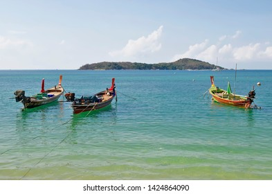 Rawai, Phuket, Thailand - April 18, 2019: Long tail boats mooring at the beach of Rawai with Koh Lon in the background.