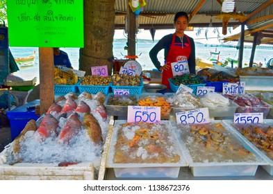 Rawai, Thailand - October 16, 2014: Fishmonger at Sea Gypsies Fish Market selling fresh fish and seafood behind her stall.