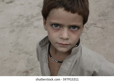 RAWALPINDI, ISLAMABAD, PAKISTAN. AUGUST 18, 2013 : An unidentified young Afghan boy peers into the camera in afghan refugees camps, Rawalpindi, Islamabad, Pakistan