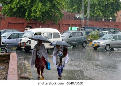 RAWALPINDI, PAKISTAN - JUL 25: Commuters passing through road during heavy downpour of monsoon season at Murree road on July 25, 2017 in Rawalpindi.