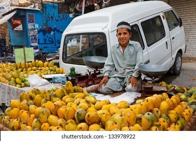 RAWALPINDI, PAKISTAN - JULY 16: Unidentified Pakistani boy sells fruits at Raja Bazaar on July 16, 2011 in Rawalpindi, Pakistan. Raja Bazaar is the main shopping area in Rawalpindi.