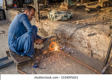 Rawalpindi, Pakistan, October 7, 2017. Man is working in his workshop and cutting Iron pieces.