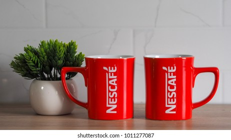 RAWANG, MALAYSIA - January 20, 2017: Two red mug of Nescafe on a wooden table.