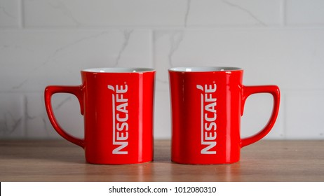 RAWANG, MALAYSIA - January 25, 2017: Two red mug of Nescafe on a wooden table and white bricks at the background.