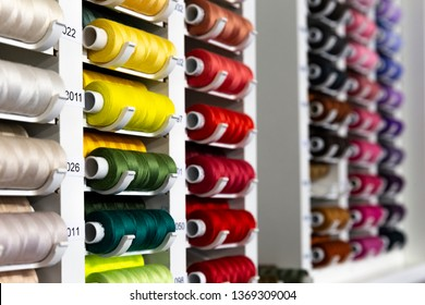 Raws of multi colored sewing threads on a stand. Industrial show room or shop.