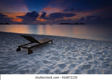 Ray of light in the beautiful sunrise morning at the tropical white sand beach with wooden chair - nature and travel concept