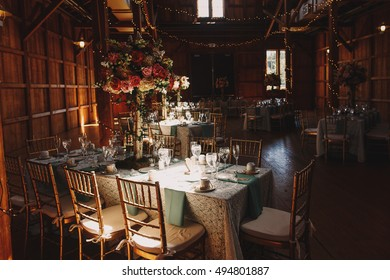 Ray of light illuminates festive served dinner table standing in the wooden hangar
