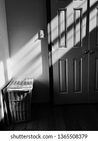 Ray of light shines down on a laundry basket black and white