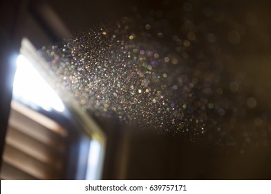 A ray of sun coming through the wooden shutters, illuminates dust on the inside of a dark room. Close up, selective focus. Vintage background.