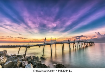 Ray sunrise on a wooden bridge with pink rays emitted before sunrise beside the wooden bridge with smooth water makes sunrise more lively and more beautiful