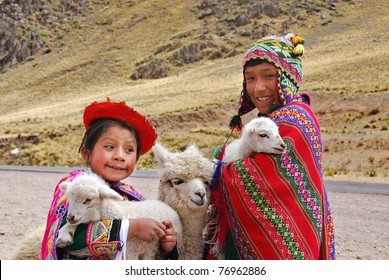 RAYA PASS, PUNO - NOVEMBER 22: Unidentified children in traditional clothing play with their animals on November 22, 2010 in Raya Pass, Puno, Peru.